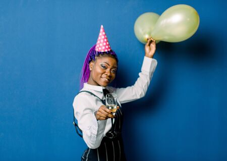 Celebration Concept, Birthday Party - Close up Portrait happy young beautiful african woman in black pants and white skirt smiling with colorful yellow party balloon. Blue Pastel studio Background.