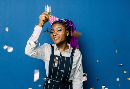 Birthday party, new year carnival. Young smiling african woman on blue background celebrating brightful event, wears elegant fashion clothes and pink party hat. Sparkling confetti, having fun, dancing Foto de archivo