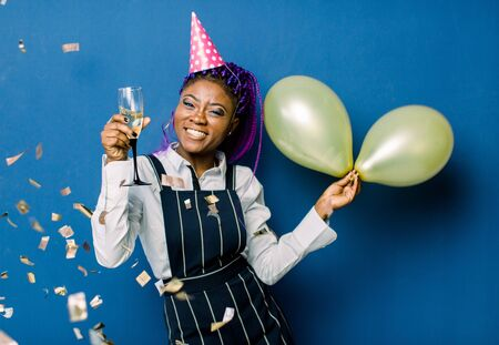 Portrait of beautiful african girl in pink party cap holding air balloons and champagne, resting at party. African woman having fun at the party with confetti on blue background
