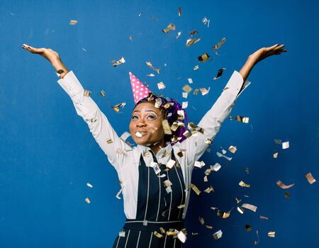 beautiful young black woman celebrating birthday or new year and chrismas party while blowing confetti decorations to camera isolated over blue background