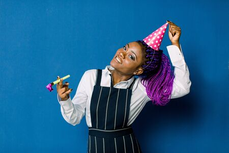 Portrait of beautiful african girl resting at party. Portrait of funny african woman in birthday hat on blue background. Celebration and party.