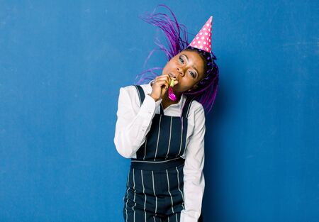 Birthday party, new year carnival. Young smiling African woman on blue background celebrating brightful event, wears elegant fashion white skirt and black pants, with pink party hat with noisemaker.