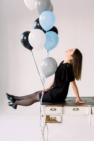 Graceful slim birthday girl in black dress posing with black, white, blue and gray balloons. Full-length portrait of adorable laughing birthday girl, sitting on the table on white background.