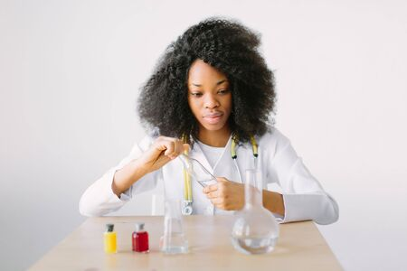 Lab assistant testing water quality. Portrait of a young beautiful African American girl researcher chemistry student carrying out research in a chemistry lab