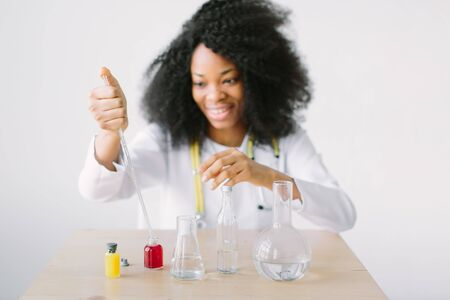 Portrait of a young beautiful African American girl researcher chemistry student carrying out research in a chemistry lab. Blood testing in the lab with young scientist
