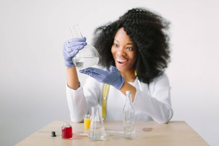 Portrait of a young beautiful African American girl researcher chemistry student carrying out research in a chemistry lab. Scientist analyzing a test-tube.