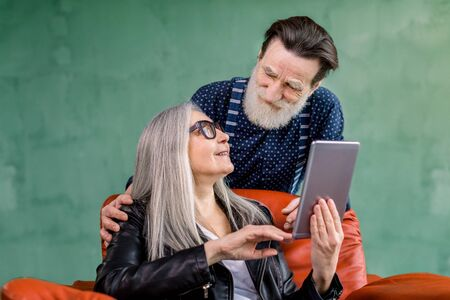 Studio shot of happy senior family couple, stylish man and woman, looking each other while browsing internet or using apps on i-pad tablet and talking each other. Woman is sitting in red chair