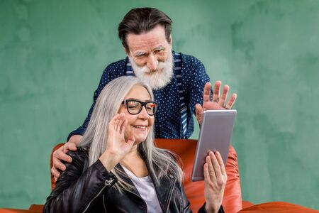 Pretty cheerful 60-70s gray haired lady sitting in soft red chair and holding tablet for video call, while handsome bearded husband leaning on chair and hugging her, waving together