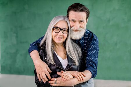 Studio shot of cheerful stylish bearded man embracing his gray haired charming wife from the back and looking at camera with smile, standing on grenn wall background