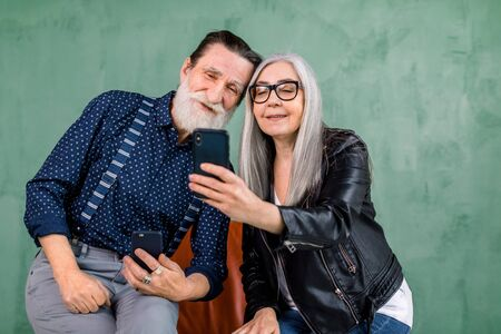 Attractive stylish couple, bearded man and gray haired lady, sitting together on the red chair and using the phone apps, looking at the smartphone screen and smiling. Isolated on green background. Foto de archivo