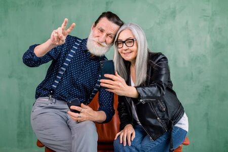 Attractive stylish couple, bearded man and gray haired lady, sitting together on the red chair and using the phone camera for making photo, and smiling. Isolated on green background. Foto de archivo