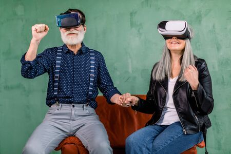 Portrait of excited elderly couple, sitting together in red chair near green wall, holding hands, with clenched fists, and enjoying the virtual reality using special virtual goggles