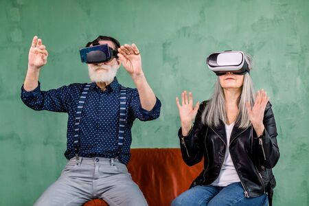 Close up portrait of stylish modern elderly man and woman, wearing trendy clothes, sitting on red chair in virtual reality goggles and touching imaginary screen in the air Foto de archivo
