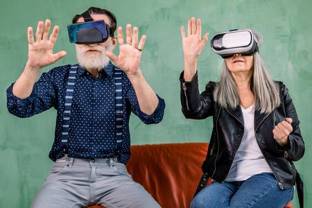 Front view of excited cheerful elderly man and woman, sitting together on red soft chair on green background, and using vr glasses headset, touching imaginary screen in the air
