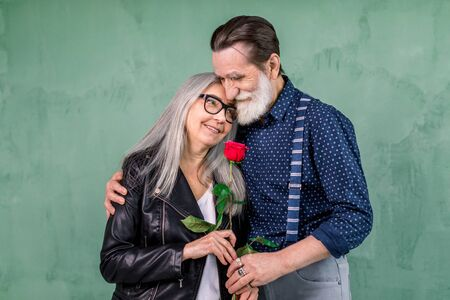 Love has no age. Romantic senior couple celebrating Saint Valentines Day. Beautiful woman and handsome man enjoying spending time together, embracing and holding red rose Foto de archivo
