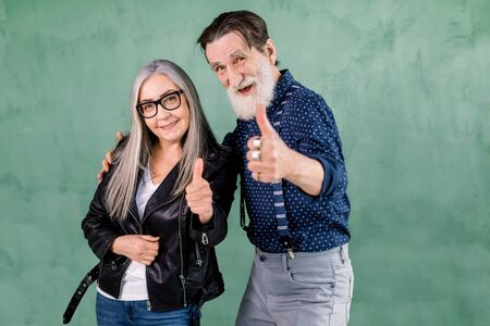 Lovely senior smiling joyful couple, handsome bearded man and pretty gray haired woman, posing to camera in front of green wall and showing their thumbs up gesture.