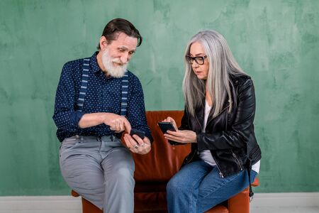 Smiling senior couple, stylish bearded man and pretty gray haired lady, enjoying review of photos on their smartphones, or showing each other how to use social networks