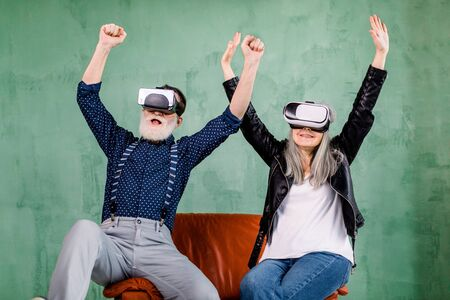 Front view of cheerful smiling senior couple in stylish trendy clothes, sitting on red soft chair and enjoying video games or 3d film using virtual reality goggles, holding their arms up
