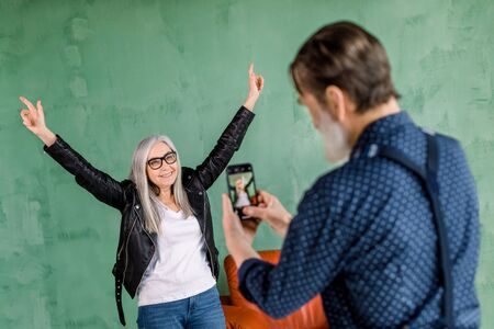 Portrait of handsome senior bearded man taking photo of his pretty woman, posing to camera on green wall background, smiling and holding her arms up