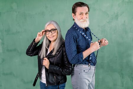 Lovely senior smiling joyful couple, handsome bearded man and pretty gray haired woman, posing to camera in front of green wall. Woman touching her eyeglasses, man pulling away his suspenders