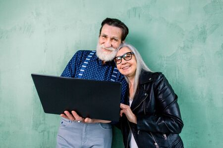 Pretty smiling senior woman in black leather jacket leaning her head on the shoulder of her handsome bearded man, while standing together near green wall and using laptop