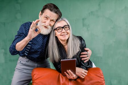 Joyful stylish mature couple spending their leisure time together. Pretty senior woman holds tablet ipad, while her handsome man embraces her and shows ok cool hand gesture.