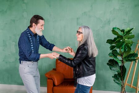 Beautiful joyful stylish senior woman with long straight gray hair, dancing together with her handsome bearded husband in the cozy room in front of green wall.