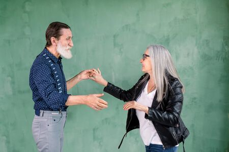 Studio family portrait. Happy smiling 60-70s bearded man and charming gray haired woman enjoying time together, while dancing holding hands, on green wall background Foto de archivo