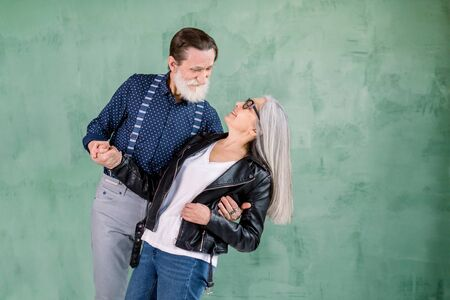 Beautiful full of harmony senior couple in love dancing. Studio shot. Graceful elderly couple, wearing stylish trendy clothes, dancing in the studio room, standing on green wall background