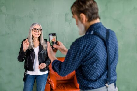 Handsome bearded senior man making photo on the phone for his beautiful wife with long gray hair, posing on the background of green wall near red chair and waving to camera