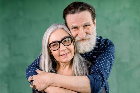 Happy family, elderly couple in love, standing on green background. Attractive smiling gray haired lady in eyeglasses looking at camera, while her handsome bearded smiling man husband embraces her