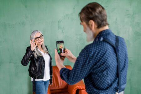 Portrait of handsome senior bearded man taking photo of his pretty woman, posing to camera on green wall background and showing ok cool hand gesture