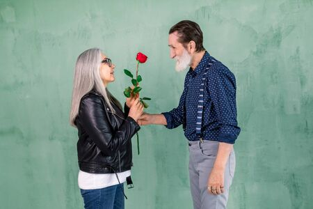 Happy senior family portrait. Handsome elderly bearded man giving beautiful red fresh rose to his charming smiling wife with long straight gray hair, standing on green wall background Foto de archivo
