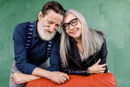 Smiling beautiful senior couple in love enjoying time together, leaning on red chair and touching foreheads, while standing in modern room in front of green wall.