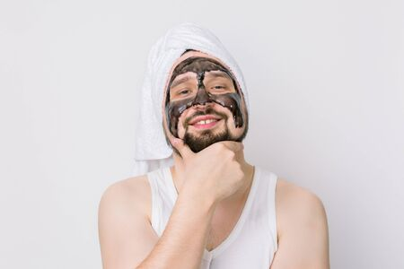 Happy proud man with black mask on the face. Photo of handsome bearded man receiving spa treatments, posing to camera on isolated white backgrund, touching his chin. Beauty and skin care concept