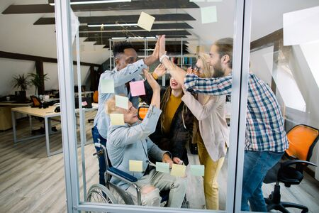 Team of young multiethnic business colleagues with one disabled guy in wheelchair, celebrating together with high fives after a brainstorming session with sticky notes on glass wall in modern office