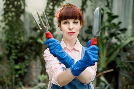 Serious concentrated young woman in blue protective gloves holding gardening tools in crossed hands and looking at camera. Gardening transplanting of plant concept
