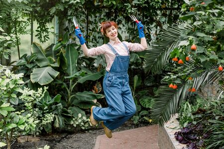 Portrait of cheerful funny young woman gardener in jeans overalls and blue rubber gloves, jumping and having fun with gardening tools indoors in greenhouse on the background of tropical plants