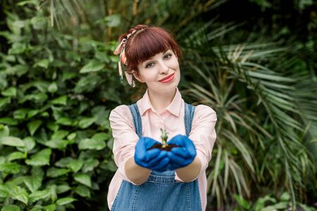 Close up of smiling charming woman gardener in jeans overalls, holding young plant succulent in soil in her hands. Female holding sapling in greenhouse, looking at camera