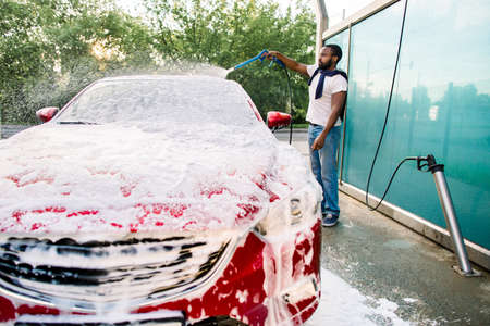 Young black man cleaning his red luxury car with foam spray outside at self car wash station. Casual African guy washing his car with high pressure sprayer and foam