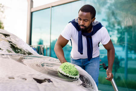 Young attractive African American man washing his modern electric luxury car in a self-service car wash station outdoors with cleaning foam and green sponge mitten