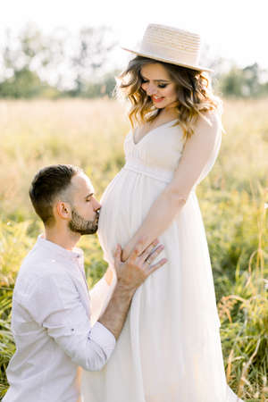 Young couple in the summer field. Handsome man is kissing the belly of his charming pregnant wife in straw hat and white dress Stockfoto