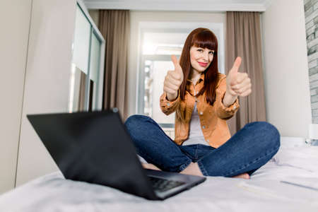 Smiling woman showing her thumbs up to camera, while sitting on the bed in light home bedroom, and having fun work or study with a laptop computer online. Distance learning, work