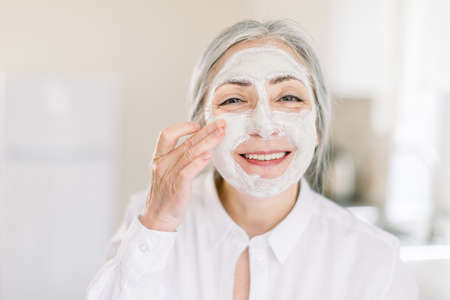 Close up beauty portrait of smiling pretty senior gray haired woman, applying mud nourishing facial mask on her face with hands, posing to camera on the background of home interior