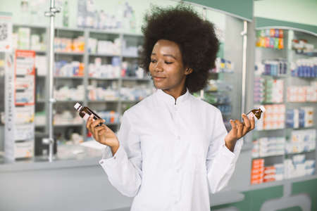 Which medicine is better, pharmacy, drug concept. Pretty African woman pharmacist or chemist choosing between two drugs in bottles, while standing in interior of modern pharmacy Фото со стока
