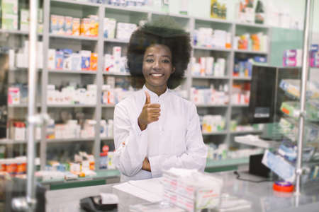 Portrait of smiling professional African female pharmacist in modern drugstore, standing behind the glass at the counter, and showing her thumb up