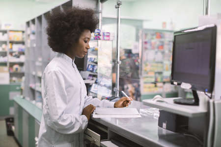 Portrait of young professional concentrated African female pharmacist working with computer behind counter in pharmacy, making notes and medicines order