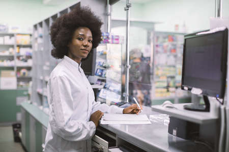 Portrait of a happy African American woman pharmacist writing prescription at workplace in modern pharmacy, looking at camera with smile