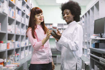 Young attractive African female pharmacist talking with a beautiful girl client in modern light pharmacy, offering good safety medicine. Pharmaceutical care concept