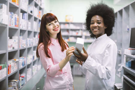 Medicine, healthcare and people concept. Young black woman apothecary with medicine box and female customer at pharmacy. Woman buyer consults with female pharmacist in drugstore